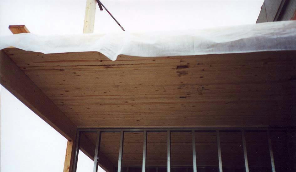 Massivtræelementer anvendt i etageadskillelsen beskyttet mod regnpåvirkninger ved hjælp af plastik.