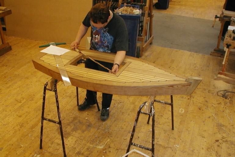 Elev tager mål til model af træbåd
