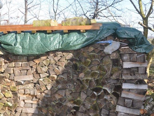 Brændestakken overdækkes med presenning der beskytter mod regn. Siderne skal være åbne for optimal ventilation og tørring. Foto: Træ.dkog åbne sider